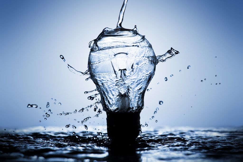 A lightbulb cracks as water is poured over it forming a pool below it.